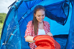 Happy young woman sitting in tent at camping Stock Photos