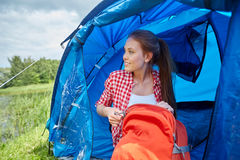 Happy young woman sitting in tent at camping Stock Images
