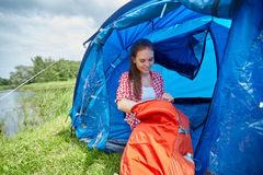 Happy young woman sitting in tent at camping Stock Image