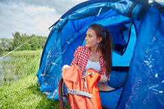 Happy young woman sitting in tent at camping Royalty Free Stock Photo