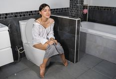 Happy woman sitting on a toilet stock photography