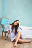 Happy young woman sitting on wood floor and relaxing at home Royalty Free Stock Photography