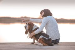 Happy young woman sitting on the wooden pier with her dog Basset Hound. Woman with puppy. Young woman sitting on the wooden pier with her dog Basset Hound. Woman stock photo