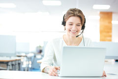 Happy young woman sitting and working with laptop using headset Royalty Free Stock Photography