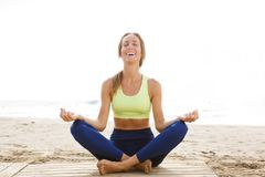Happy young woman sitting in yoga pose at the beach. Portrait of happy young woman sitting in yoga pose at the beach Royalty Free Stock Images
