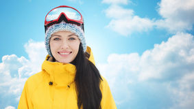 Happy young woman in ski goggles over blue sky Stock Images