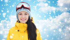Happy young woman in ski goggles over blue sky. Winter, leisure, sport and people concept - happy young woman in ski goggles over blue sky and clouds background Royalty Free Stock Images
