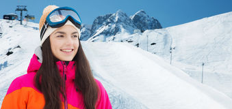 Happy young woman in ski goggles over mountains Royalty Free Stock Photos