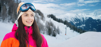 Happy young woman in ski goggles over mountains Royalty Free Stock Image