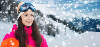 Happy young woman in ski goggles over mountains Stock Photos