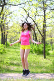 Happy young woman with skipping rope at summer park Stock Images