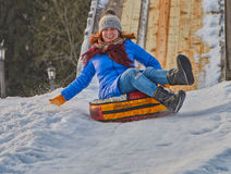 Happy Young Woman Sleigh Ride. Happy Young Woman on a fast Sleigh Ride down the icy slope Royalty Free Stock Image