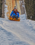 Happy Young Woman Sleigh Ride. Happy Young Woman on a fast Sleigh Ride down the icy slope Stock Photo
