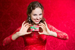 Happy young woman with a small gift in a red dress. Stock Photo