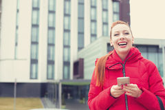 Happy young woman with smart phone outdoors on a city background. Royalty Free Stock Photos