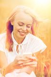 Happy young woman with smartphone on cereal field Stock Image