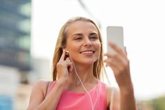 Happy young woman with smartphone and earphones Royalty Free Stock Photography