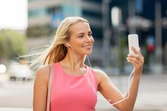 Happy young woman with smartphone and earphones Royalty Free Stock Images