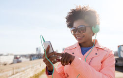 Happy young woman with smartphone and headphones Royalty Free Stock Images