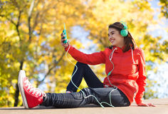 Happy young woman with smartphone and headphones Royalty Free Stock Photography