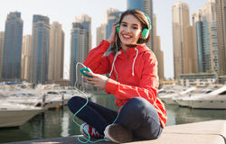 Happy young woman with smartphone and headphones Stock Photos
