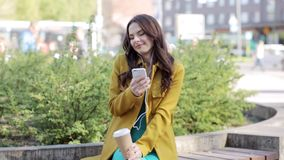 Happy young woman with smartphone and headphones stock video