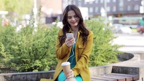 Happy young woman with smartphone and headphones stock footage