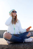 Happy young woman with smartphone and headphones Stock Photography
