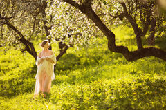 Happy young woman smelling a flower on an apple tree Stock Images