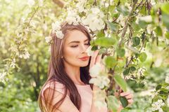 Happy young woman smelling flowers in blossom spring flowers stock image