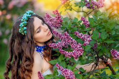 Happy young woman smelling a spring branch of lilac flowers Stock Image