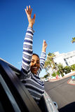 Happy young woman smiling with arms raised outside car window Stock Image