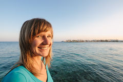 Happy young woman smiling looking at camera on beach on sunset Stock Photos