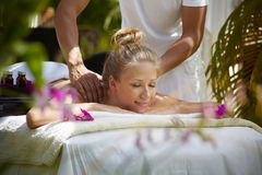 Happy young woman smiling during massage in spa Royalty Free Stock Photos
