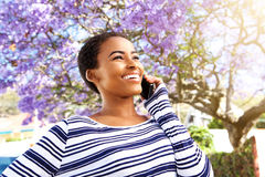Happy young woman smiling outside with cellphone Stock Photo