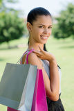 Happy young woman smiling with shopping bags. Consumerism, portrait of happy young woman smiling with shopping bags Stock Photo