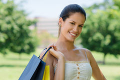 Happy young woman smiling with shopping bags. Consumerism, portrait of happy young woman smiling with shopping bags Royalty Free Stock Photos