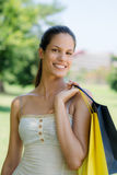Happy young woman smiling with shopping bags. Consumerism, portrait of happy young woman smiling at camera with shopping bags Royalty Free Stock Images