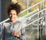 Happy young woman smiling with water bottle Stock Photography