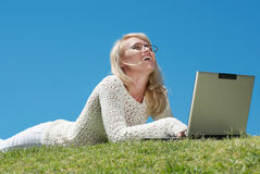 Happy young woman smiling and working on a laptop Royalty Free Stock Image