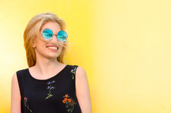 Happy young woman smiling on a yellow wall with sunglasses Royalty Free Stock Image