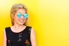 Happy young woman smiling on a yellow wall with sunglasses Stock Image