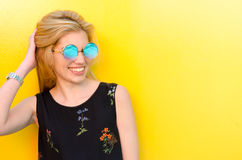 Happy young woman smiling on a yellow wall with sunglasses Stock Photography