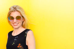 Happy young woman smiling on a yellow wall with sunglasses Royalty Free Stock Images