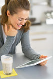 Happy young woman with smoothie using tablet pc Royalty Free Stock Images