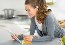 Happy young woman with smoothie using tablet pc in kitchen Stock Images