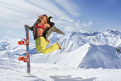 Happy young woman with snowboard jumping in winter sportswear. Smiling woman with snowboard jumping in mid air against of snowy mountains.Wearing bikini top and royalty free stock photos