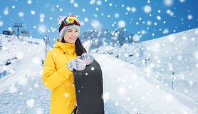 Happy young woman with snowboard over mountains Stock Photo