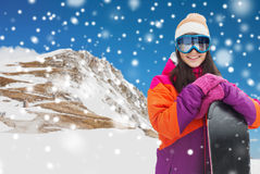 Happy young woman with snowboard over mountains Stock Image