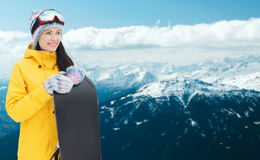 Happy young woman with snowboard over mountains Royalty Free Stock Photography